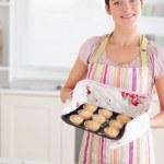 Beautiful brunette woman showing muffins — Stock Photo