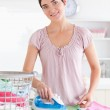 Smiling Woman ironing clothes — Stock Photo