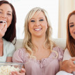 Charming Friends lounging on a sofa watching a movie — Stock Photo