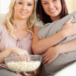 Stock Photo: Smiling women lounging on sofwatching movie