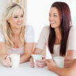 Smiling young Women sitting at a table with cups — Stock Photo #11188778