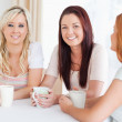 Charming young Women sitting at a table with cups — Stock Photo #11188780
