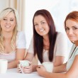 Women sitting at a table drinking coffee — Stock Photo