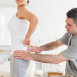 Chiropractor examining a charming woman's back — Stock Photo