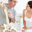 Chiropractor explaining the spine to his patient — Stock Photo #11189104