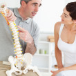 Chiropractor explaining the spine to his patient — Stock Photo