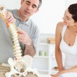Chiropractor explaining the spine to a woman — Stock Photo