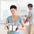 Cute Woman holding a pot while man is washing the dishes — Stock Photo