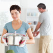 Cute wife holding a pot while her husband is washing the dishes — Stock Photo