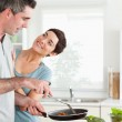 Woman smiling at her pan-holding husband — Stock Photo