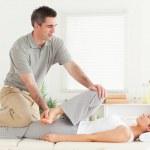 Chiropractor stretching a female customer's leg — Stock Photo