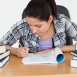 Young student writing into her exercise book - Stock Photo