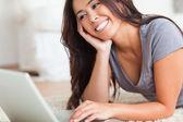 Nahaufnahme einer lächelnden frau liegend auf einem teppich mit notebook — Stockfoto
