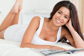 Close up of a charming woman lying on bed reading a magazine loo — Stock Photo