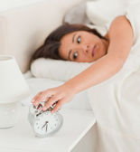 Charming woman waking under sheet turning off alarm clock — Stock Photo