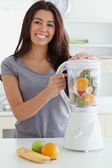 Good looking woman using a blender while standing — Stock Photo