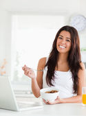 Gorgeous woman enjoying a bowl of cereals while relaxing with he — Stock Photo