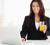Pretty woman in suit relaxing with her laptop while holding a gl — Stock Photo