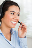 Portrait of an attractive woman with a headset helping customers — Stock Photo
