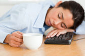 Beautiful woman sleeping on a keyboard while holding a cup of co — Stock Photo
