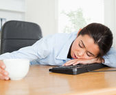 Frontal view of a beautiful woman sleeping on a keyboard while h — Stock Photo