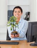Schöne frau gedrückt, dass eine pflanze in die kamera schaut — Stockfoto