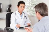 Patienten geben seine schöne frau doktor ein stück papier — Stockfoto