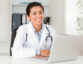 Good looking female doctor working with her laptop while posing — Stock Photo