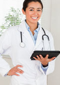 Beautiful female doctor with a stethoscope holding a notebook wh — Stock Photo