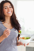 Pretty woman enjoying a bowl of salad while standing — Stock Photo