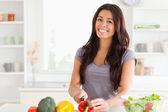 Mujer atractiva cocinar verduras mientras está parado — Foto de Stock