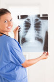 Charming doctor smiling at the camera holding a x-ray — Stock Photo