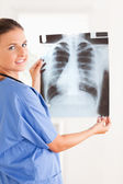Charming doctor smiling into the camera holding a x-ray — Stock Photo