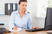 Kobieta siedzi za biurkiem, jej patrząc na jej ekran — Zdjęcie stockowe