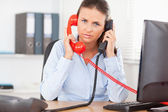 Secretary telephoning with two telephones — Stock Photo