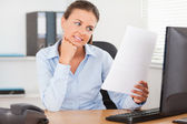 Charming businesswoman reading a paper — Stock Photo