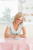 Mujer sonriente prueba de lectura de un texto — Foto de Stock