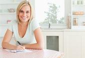 Una mujer encantadora prueba de lectura de un texto se ve en cámara — Foto de Stock
