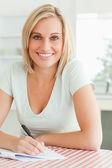 Söt kvinna korrekturläsning en text ler in i kameran — Stockfoto