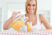 Close up of a smiling woman sitting at a table filling orange ju — Stock Photo