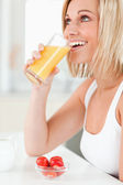 Woman drinking glass of orange juice — Stock Photo
