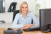 Smiling woman sitting behind a desk — Stock Photo