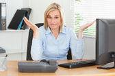Young blonde woman sitting behind desk not having a clue what to — Stock Photo