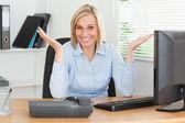 どのような手掛かりを持っていない机の後ろに座っている金髪の女性の笑みを浮かべてください。 — ストック写真