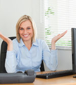 Smiling woman sitting behind desk not having a clue what to do n — Stock Photo
