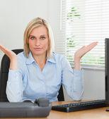 Mulher séria sentado atrás da mesa, não tendo a menor idéia o que fazer n — Foto Stock