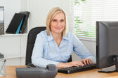 Working woman in front of a screen looks into camera — Stock Photo