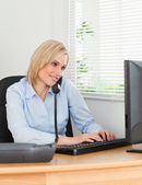 Smiling businesswoman on the phone while typing looks at screen — Stock Photo