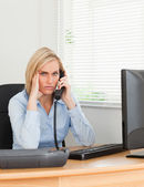 Blonde businesswoman on phone while having headache looks into c — Stock Photo