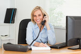 Cute businesswoman on phone writing something down looks into ca — Stock Photo